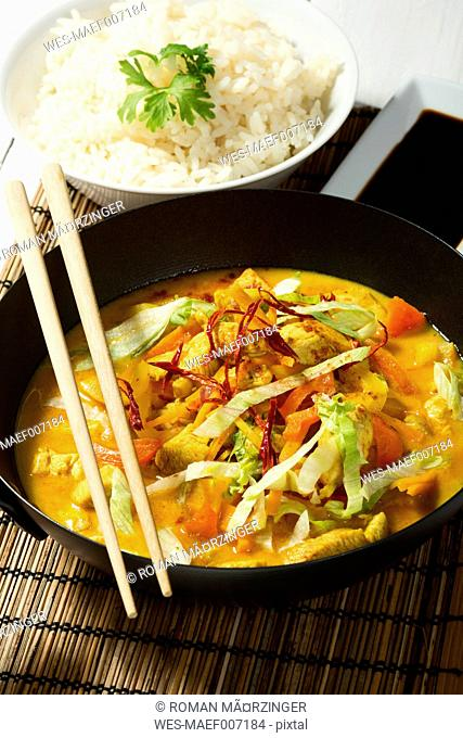 Spicy chicken with red curry, peppers, chillies, carrots, coconut milk and bowl of rice on table mat