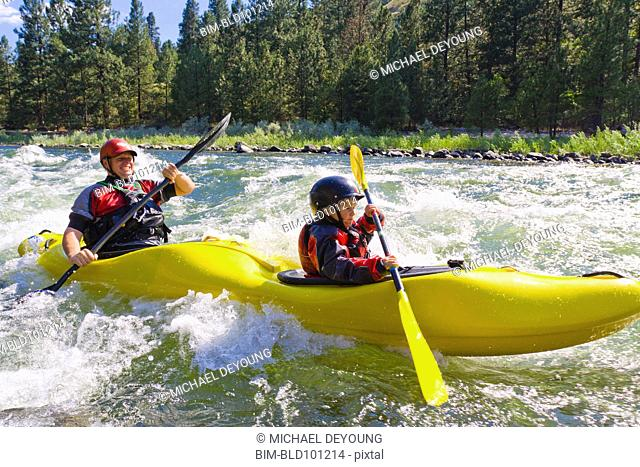 Caucasian father and son kayaking in river
