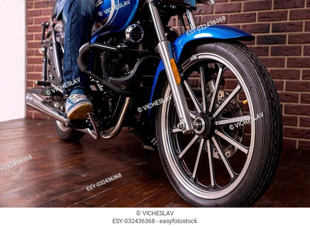 Man Riding a Blue Sports Motorbike on the House Wooden Floor, Emphasizing the Wheel in Close up