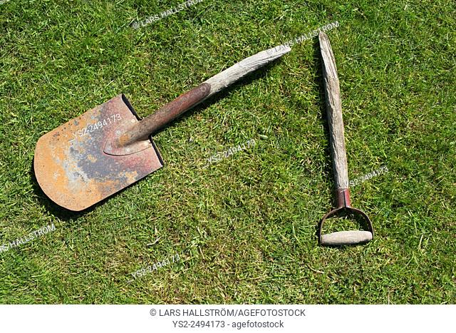 Broken garden shovel lying on green grass