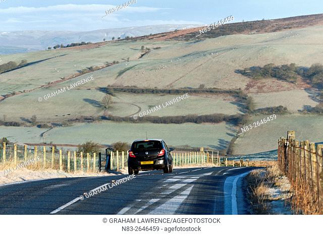 A motorist drives through a winter landscape on the Mynydd Epynt moorland, Powys, Wales, UK