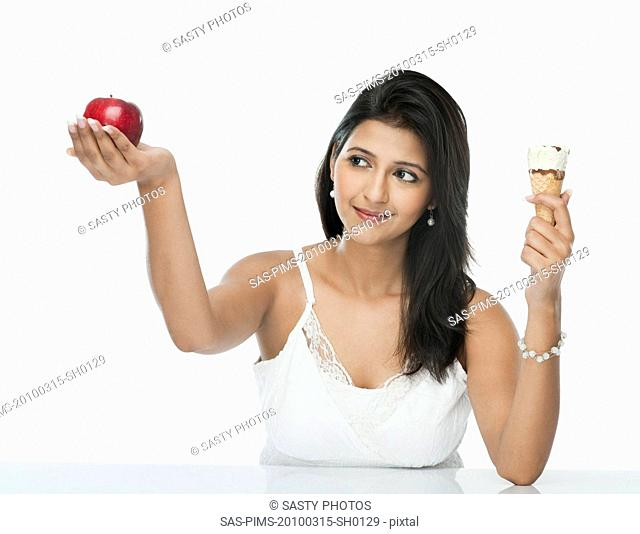 Woman comparing an ice cream cone with an apple