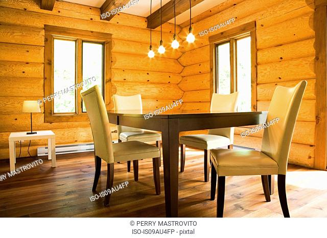 Dining table and chairs with modern lighting in Eastern white pine log cabin