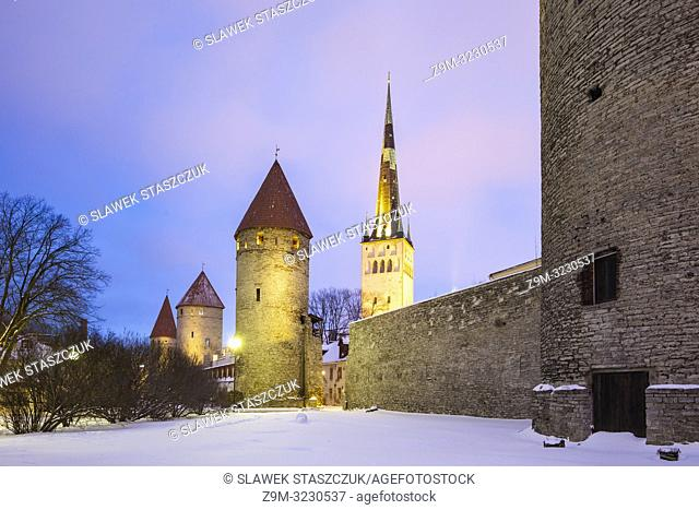 Winter evening at the city walls in Tallinn old town, Estonia. St Olaf's church tower in the distance