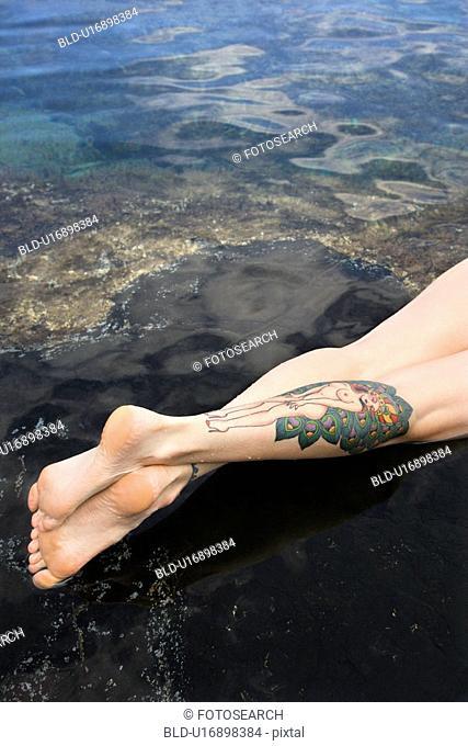 Legs of tattooed woman lying in tidal pool