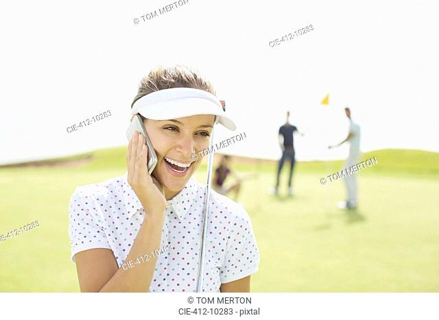 Woman talking on cell phone on golf course