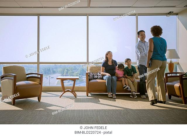 Doctor greeting patients in waiting room