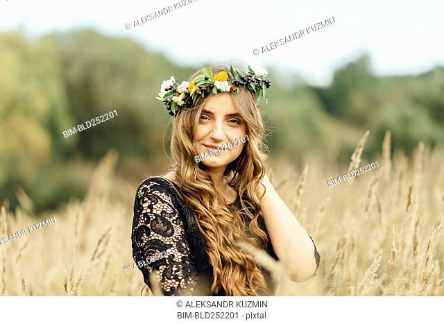 Middle Eastern woman wearing flower crown in field