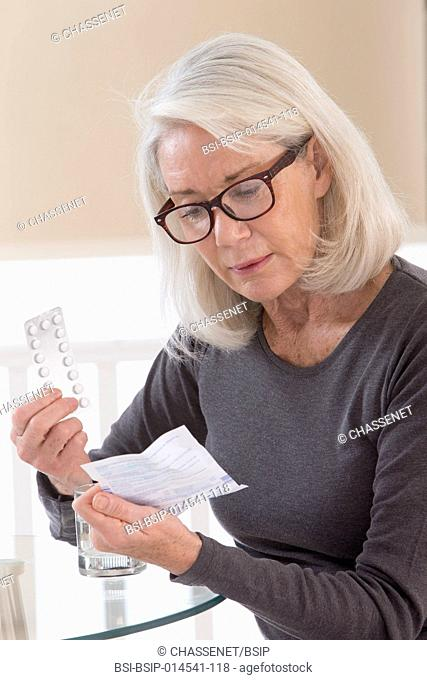 Senior woman reading medication instruction sheet