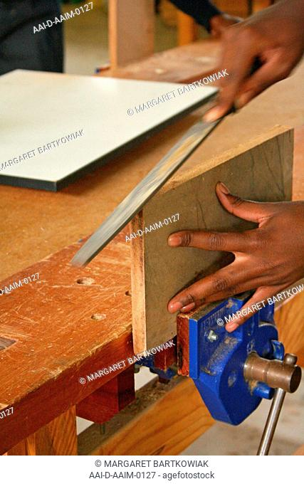 School boy filing wood in woodwork classroom, St Mark's School, Mbabane, Hhohho, Kingdom of Swaziland