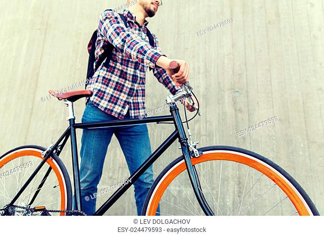 people, travel, tourism, leisure and lifestyle - close up of young hipster man with fixed gear bike and backpack on city street