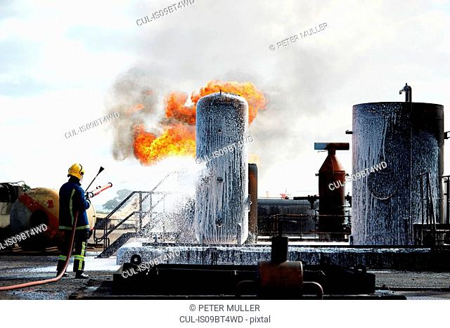 Fireman training to put out fire on burning tanks, Darlington, UK