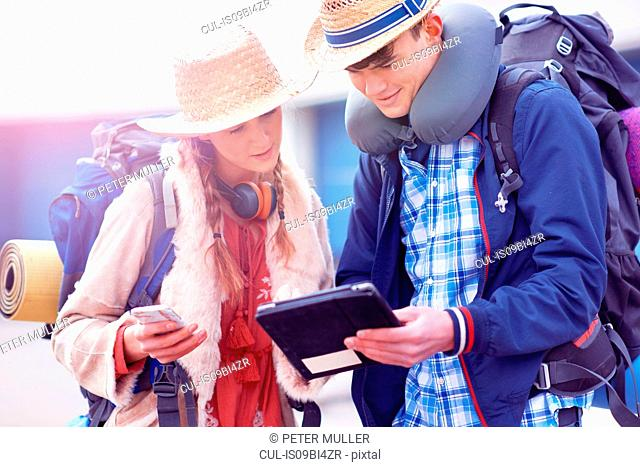 Backpacker couple using digital tablet