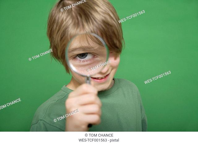 Close up of boy looking through magnifying glass against green background