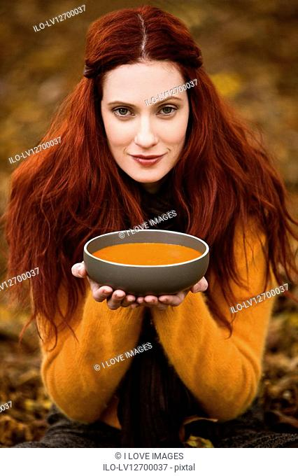 A young woman holding a bowl of soup