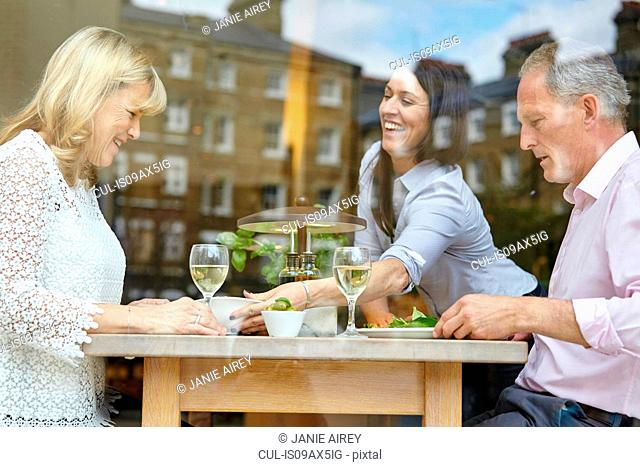 Waitress serving lunch to mature dating couple at restaurant table, London, UK