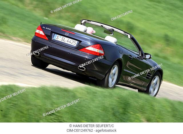 Mercedes SL 500, model year 2006-, black, open top, driving, diagonal from the back, rear view, country road