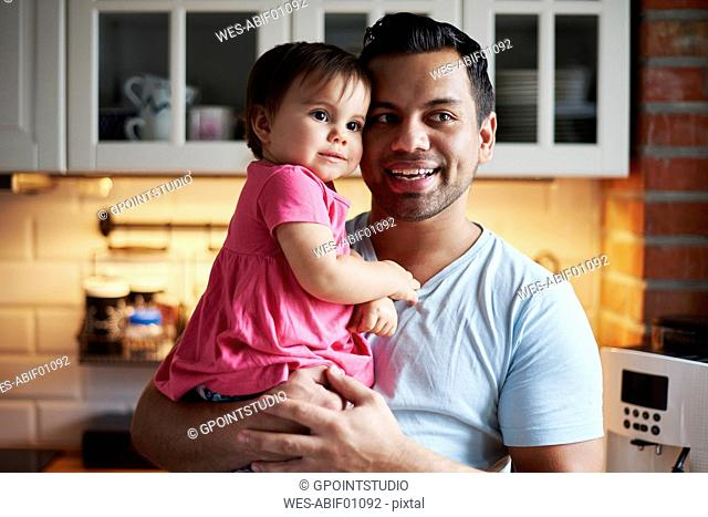 Smiling father holding baby girl in kitchen at home