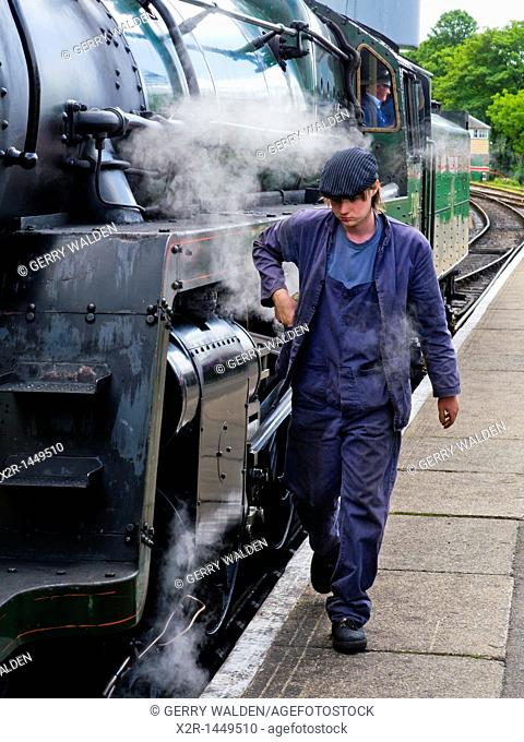 A woker on the Mid Hants Railway walking alongside steam engine 73096 whilst at Alresford Station on the Watercress Line