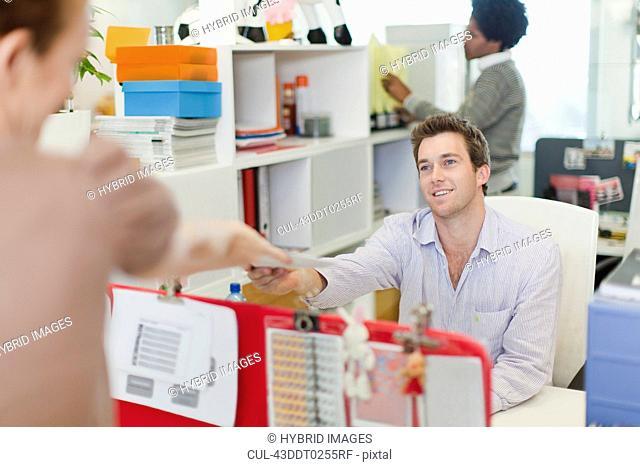 Businesswoman handing over mail