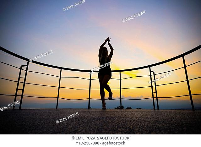 Happy young woman silhouetting against sunset sky