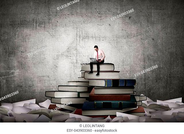 Asian business person working with laptop sit on top of book. Idea and knowledge concept