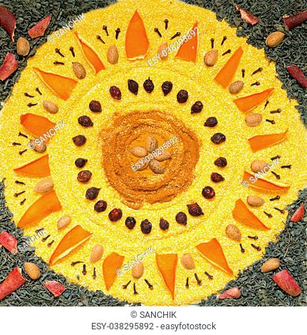 Mandala created from spices, dried fruit, tea, coffee and other products. The symbol of the sun. Top view