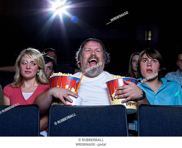 Large man with buckets of popcorn and drink at movie theater between couple