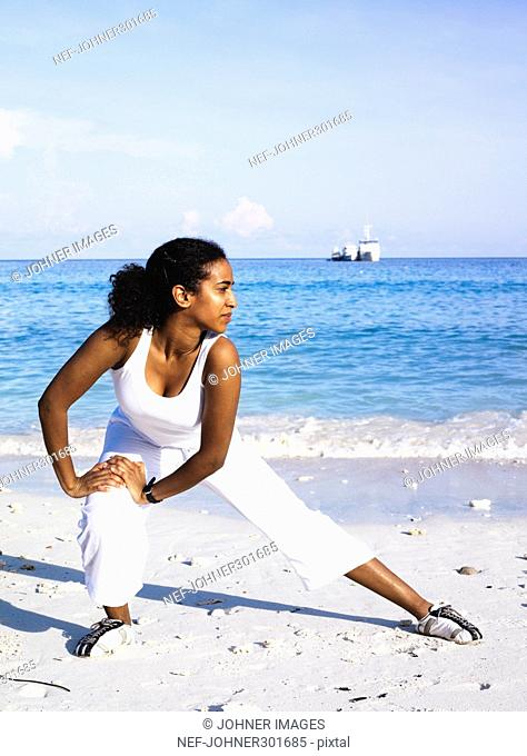 A woman stretching on a beach
