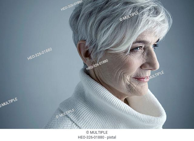 Portrait pensive Caucasian senior woman with short white hair looking away in white cowl neck sweater