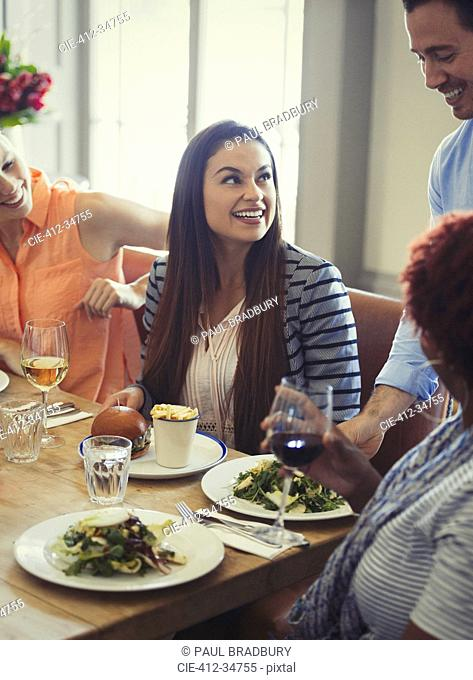 Waiter serving salads to women dining at restaurant table