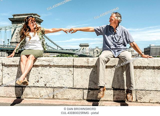 Older couple holding hands on bridge
