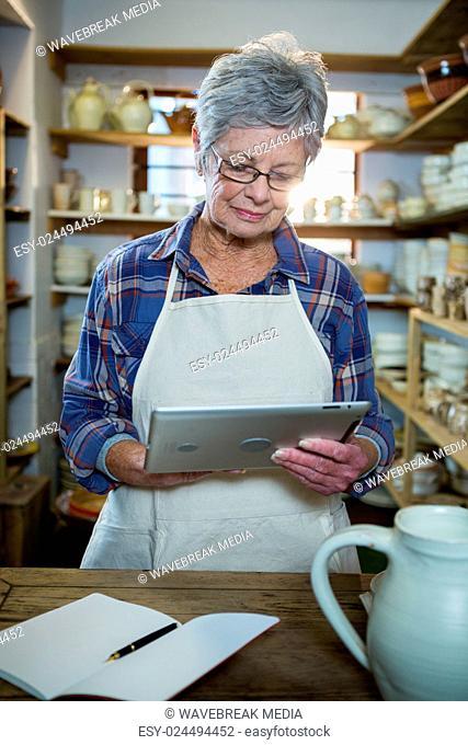 Attentive female potter using digital tablet