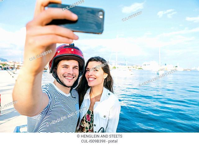 Young moped couple taking selfie on harbour, Split, Dalmatia, Croatia