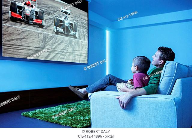 Father and son watching television in living room