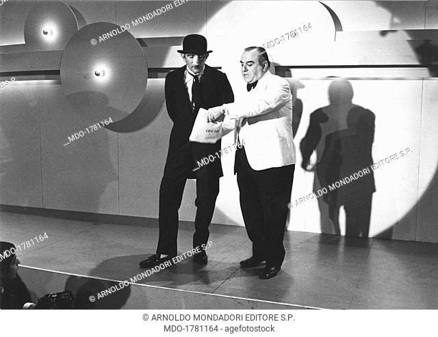 The Italian actors Carlo Campanini and Walter Chiari are guest stars of the television show Un disco per l'estate; the couple is playing the role of the...