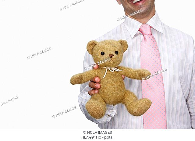 Mid section view of a businessman holding a teddy bear