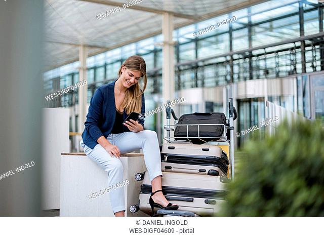 Smiling young businesswoman sitting outdoors with cell phone and suitcase