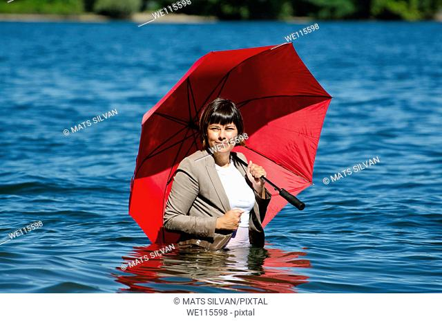 Woman standing in the water with a red umbrella and with a suit