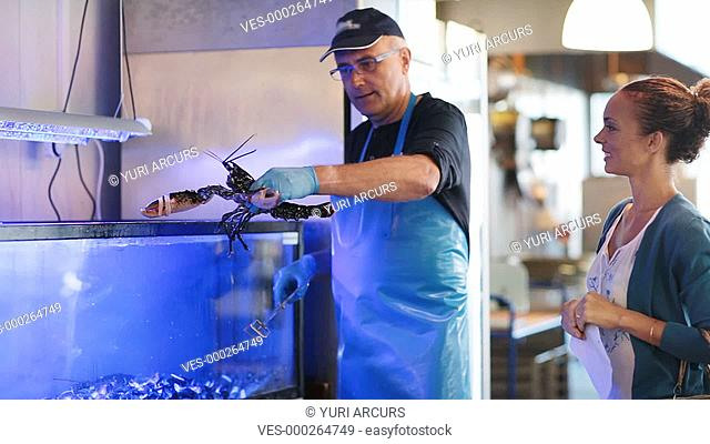 Happy fishmonger showing a live lobster to a female customer
