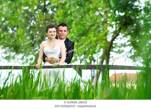 The bride and groom posing on a wooden bridge in nature and looking at camera while the groom is standing behind the bride and holding her around the waist
