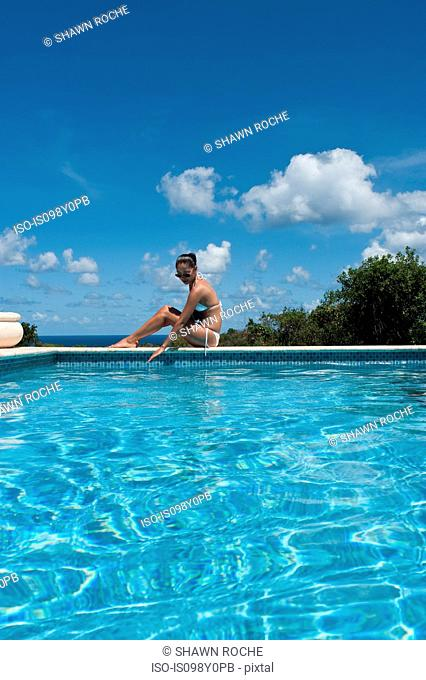 Young woman sitting on edge of pool