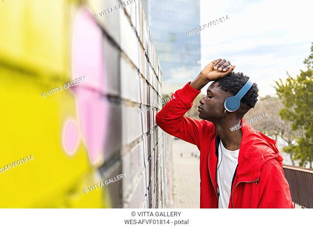 Young black man leaning on wall, listening music with headphones