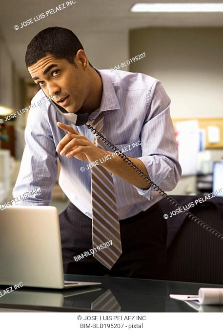 Mixed race businessman using laptop and talking on telephone