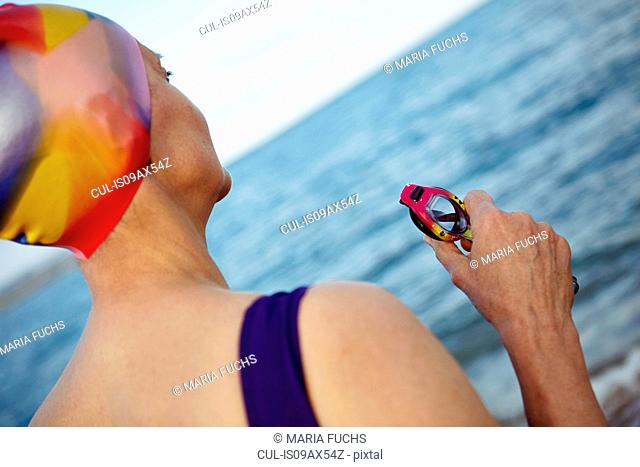 Mature woman wearing swimming costume, swimming hat and holding swimming goggles, standing beside the sea, rear view
