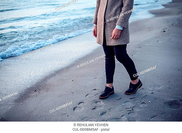 Young woman walking on beach, leaving footprints in wet sand, low section