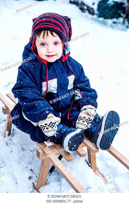 Portrait of boy wearing ski suit on toboggan