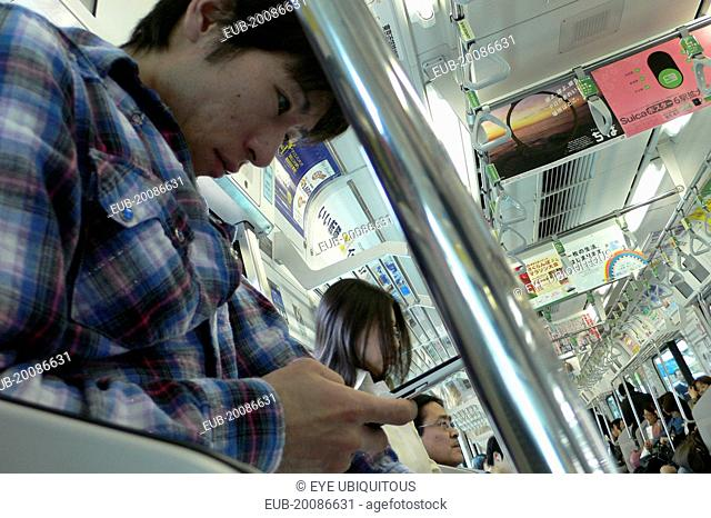 JR train, a young man uses his cell phone, text message