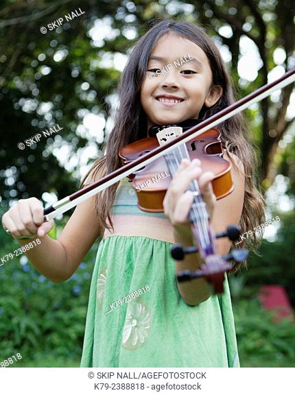 A young girl playing the violin outside