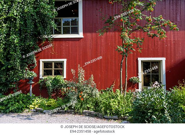 A garden and a house with red siding in île d'Orléans, Quebec, Canada